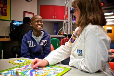 Female doctor playing Candyland while talking to a young male patient