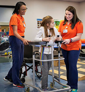 Two female therapists working with little girl in physical therapy
