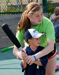 Girl helping a young boy hold a baseball bat