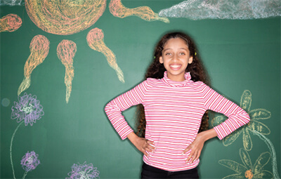 Smiling girl standing in front of a chalkboard background