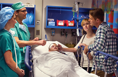 Parents talking to two surgeons while their child is in a hospital bed