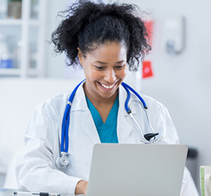 Young female doctor smiling and typing on the computer