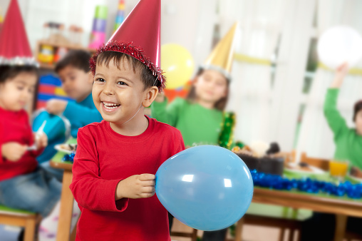 kid smiling holding balloon