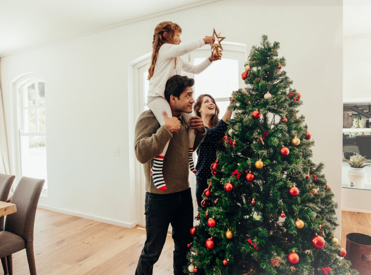 Little girl sitting on dad's shoulders adding the start to the holiday tree while mom watches